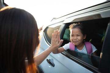 Back to school. Asian pupil girl with backpack sitting in the car waving goodbye to her mother to get ready to school.
