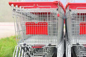 Close up of several silver shopping trolleys stacked one inside the other and photographed from behind