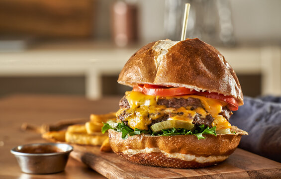 double cheeseburger with american cheese and fries on pretzel  bun