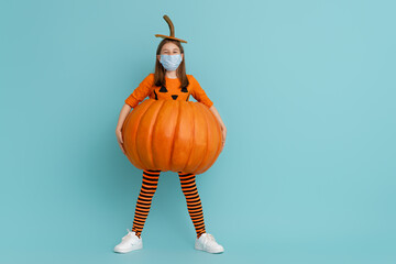 girl in pumpkin costume  wearing face mask