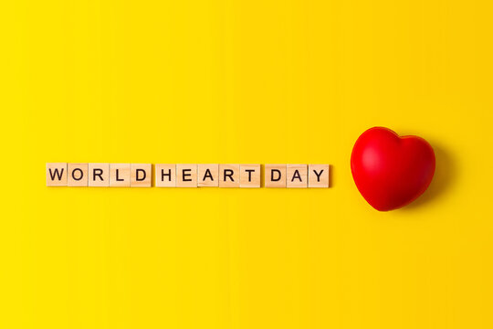 World Heart Day concept.Red heart with world heart Day text on yellow paper background