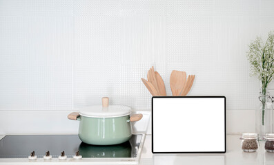 Mockup blank screen tablet on counter table in kitchen room.