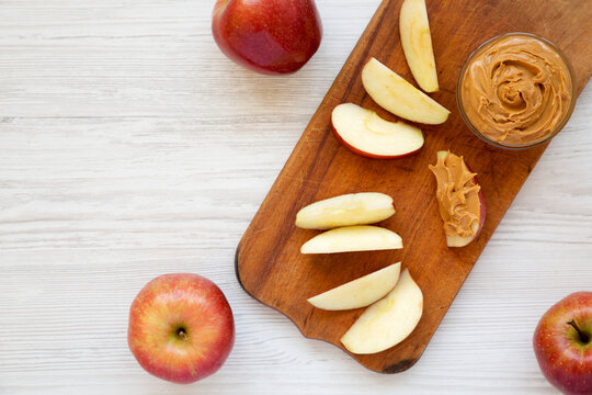 Raw Red Apples and Peanut Butter on a rustic wooden board on a white wooden table, top view. Space for text.
