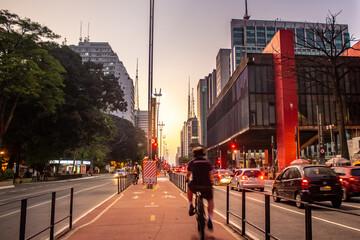 Homem andando de bicicleta na ciclovia da Avenida Paulista em frente ao Museu de Artes de São Paulo