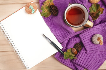 flat lay autumn notebook with fountain pen, purple sweater, metal tea mug with oak leaves, pine cones, knitted pumpkins