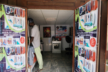 A man is seen working inside a laundry shop in Abuja