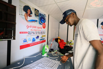 A man works inside a laundry shop in Abuja