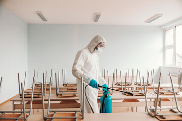 Man in sterile uniform, with gloves and mask holding sprayer and spraying with disinfectant desks and chairs in classroom.