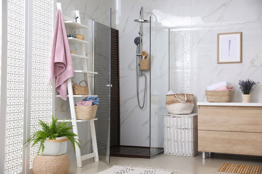 Bathroom interior with shower stall and shelving unit. Idea for design