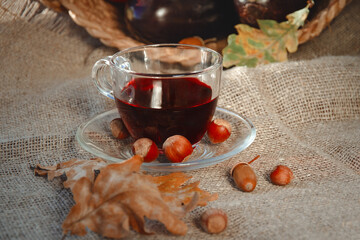 red flower tea in glass cup on burlap with nuts and autumn yellow leaves on sackcloth background