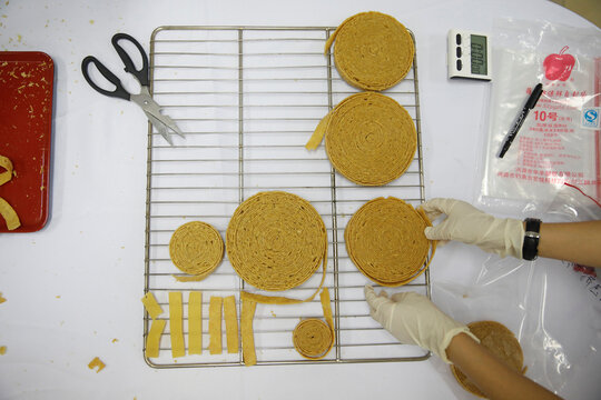 A food scientist grabs a roll of texturized vegetable protein, which is the base of the plant-based meat products offered by Zhenmeat, during a demonstration for the media of the production process in a lab at the Chinese Academy of Agricultural Sciences i