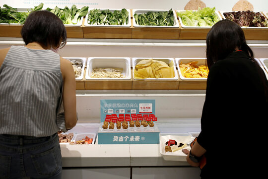 Plant-based meatballs produced by Zhenmeat are seen at the counter as customers choose the ingredients for their meal at a Hope Tree restaurant in Beijing
