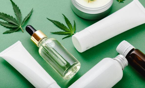 Moisturizing cream, Serum, lotion, CBD oil, essential oil cannabis leaves. Set of hemp skin care cosmetics in white mockup packaging. Flat lay on green background