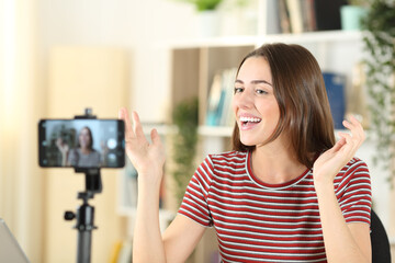Happy influencer recording video at home