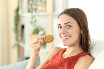 Happy woman holding a cereal cookie looking at you