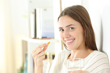 Happy woman holding a vitamin pill ready to eat it