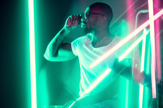 Geometric lines. Cinematic portrait of stylish young man in neon lighted room. Bright neoned colors. African-american model, musician indoors. Youth culture in party, festival style and music concept.