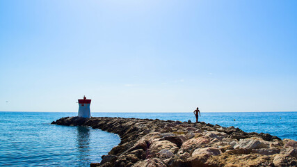 Silhouette of a young guy on the stones of the breakwater,  by the end of which stands a lighthouse.