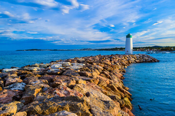 Lighthouse is located on the rocks of the breakwater that protects the entrance to the marina. Seascape with beautiful sky at sunset.