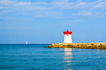 The lighthouse, located on the rocks of the breakwater, is reflected in the water.