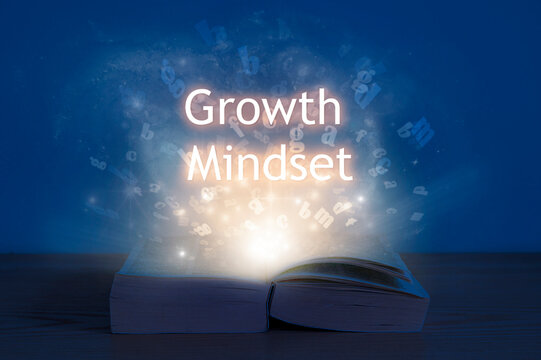 Growth mindset, education concept. Light coming from open book with words growth mindset.