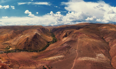 Aerial drone panorama of colorful eroded landform of Altai mountains with yellow, brown and red colors. Nature landscape in popular tourist location called Mars, near the border with Mongolia, Chagan