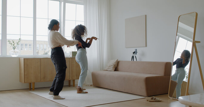 Two African-American Black girls recording trendy dance moves for social media account