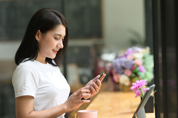 Portrait of woman smiling while   using smart phone in office.