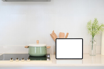 Kitchenware and tablet with white screen on modern kitchen counter.