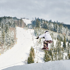 Male skier in winter jacket and helmet skiing downhill in snowy mountains with beautiful snowy trees and hills on background. Man freerider on skis making jump while sliding down snow-covered slope