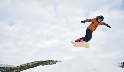 Concept of extreme kinds of sport. Snowboarder wearing colorful clothing flying up high with snowboard against cloudy sky. Low angle view, copy space. Love for sport