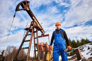 Portrait of oil well enginner in protective helmet and work overalls holding industrial wrench. Male worker standing near petroleum pump jack under beautiful sky. Concept of petroleum industry.