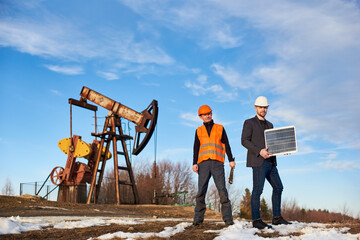 Two men on oil field with pump jack on background. Businessman holding portable solar panel, oil well operator with wrench in hand. Concept of petroleum industry and alternative energy sources.