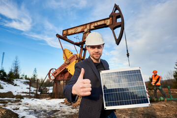 Businessman holding portable solar panel, showing approval gesture. Engineer working with pump jack on territory of oil field on background. Concept of petroleum industry, alternative energy sources.