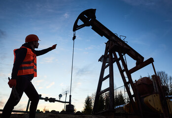 Low angle side view snapshot of an oil engineer wearing orange vest and a helmet, pointing at the oil rig and holding a pipe wrench in other hand against beautiful evening sky. Petroleum industry.