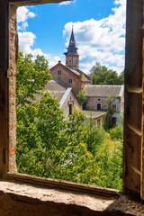 Old abandoned Catholic Church overgrown with greenery