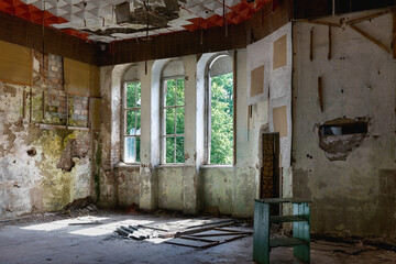 Interior of a living room with three windows of an abandoned house