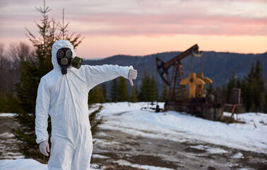 Researcher wearing white coverall, gloves and a gas mask standing in oil field in mountainous region, showing thumb down, purple horizon on background, concept of emission of oil industry