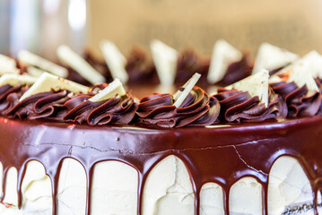 A rich decadent chocolate cake with chocolate swirls and shards of white icing