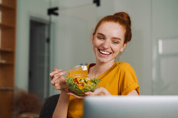 Image of laughing redhead girl eating salad while working with laptop