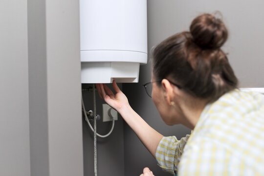Home water heater, woman regulates the temperature on an electric water heater