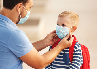 Man putting medical mask on son before going to school