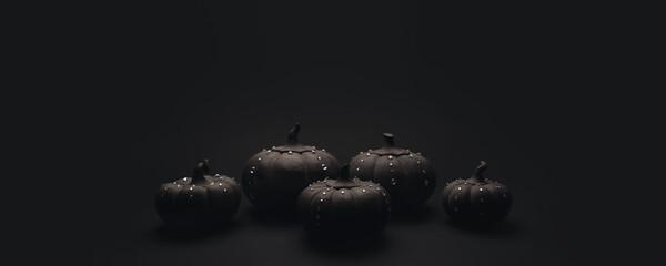 Ceramic pumpkins with rhinestones on a black background. Minimalistic background for autumn holidays with space for text.