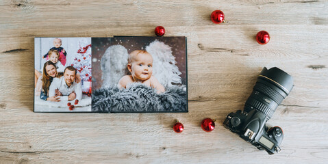 cute baby christmas angel and young family in photo book