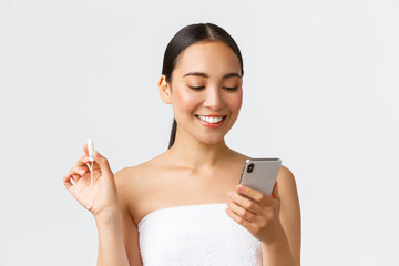 Beauty, personal and intimate care, mobile application concept. Smiling pretty asian girl having...