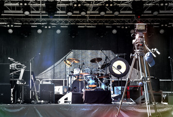 Empty illuminated stage with drum kit, microphones and film camera