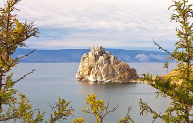 Siberian Baikal Lake in an autumn day. Olkhon Island in September. View of the natural landmark Shamanka Rock framed by yellowed larches in the sunset light. Beautiful landscape
