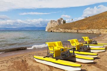 Baikal Lake at September windy day. Island Olkhon. Khuzhir village. Yellow pedal boats  on a sandy beach near the famous Shamanka Rock or Cape Burhan