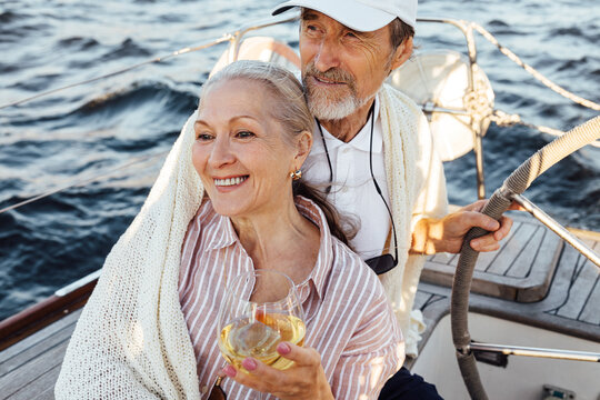 Elderly couple sitting together on a private yacht and wrapped in a plaid. Smiling caucasian woman drinking a wine while her husband stearing a wheel.