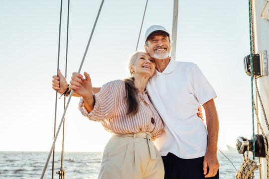 Happy mature couple embracing each other and looking away. Two people standing on sailboat and smiling.
